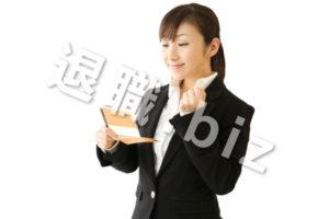 通帳を見てガッツポーズをするスーツの女性