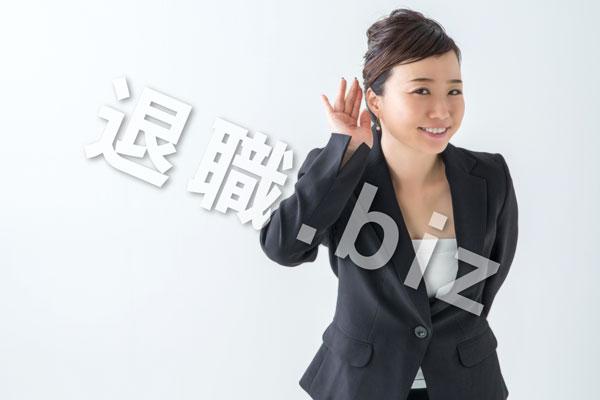 左耳にてを当てるスーツの女性