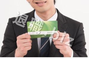 通帳を見て笑顔なスーツの男性