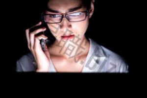 夜電話かける女性
